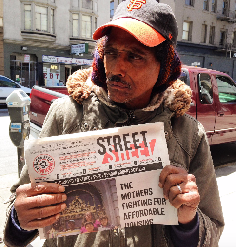 A vendor holding a copy of the Street Sheet