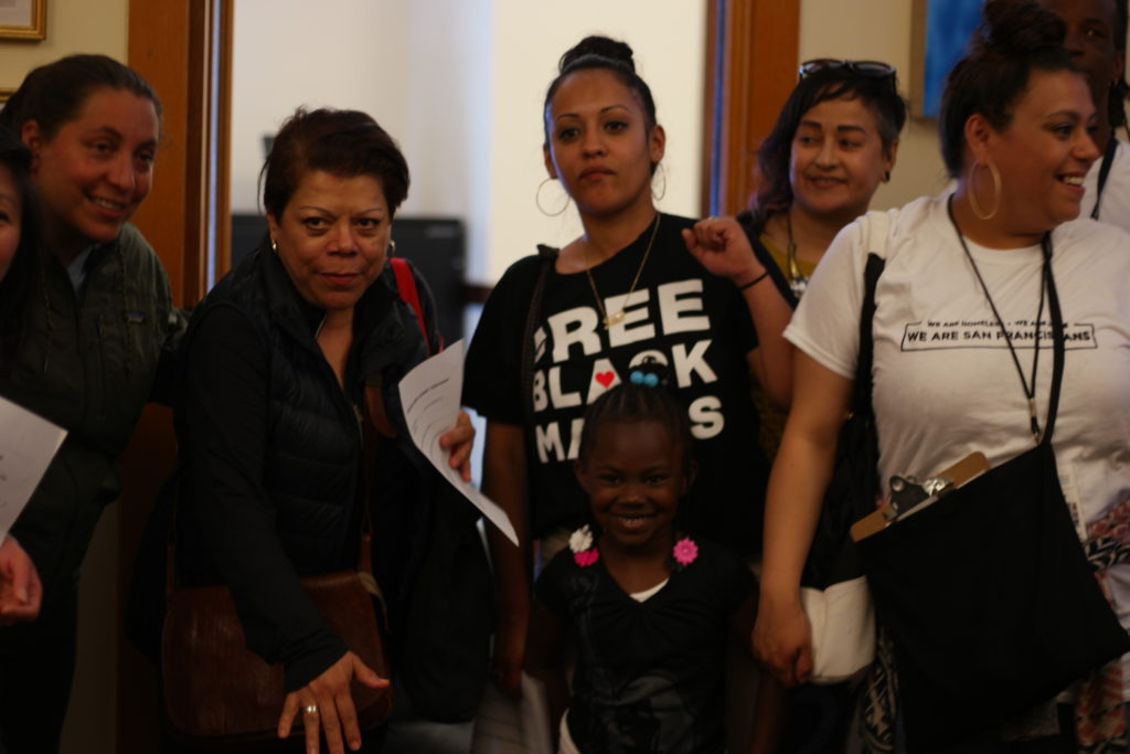 group of people, including a young child, gather inside City Hall as they visit politicians offices to demand housing and services for homeless families.