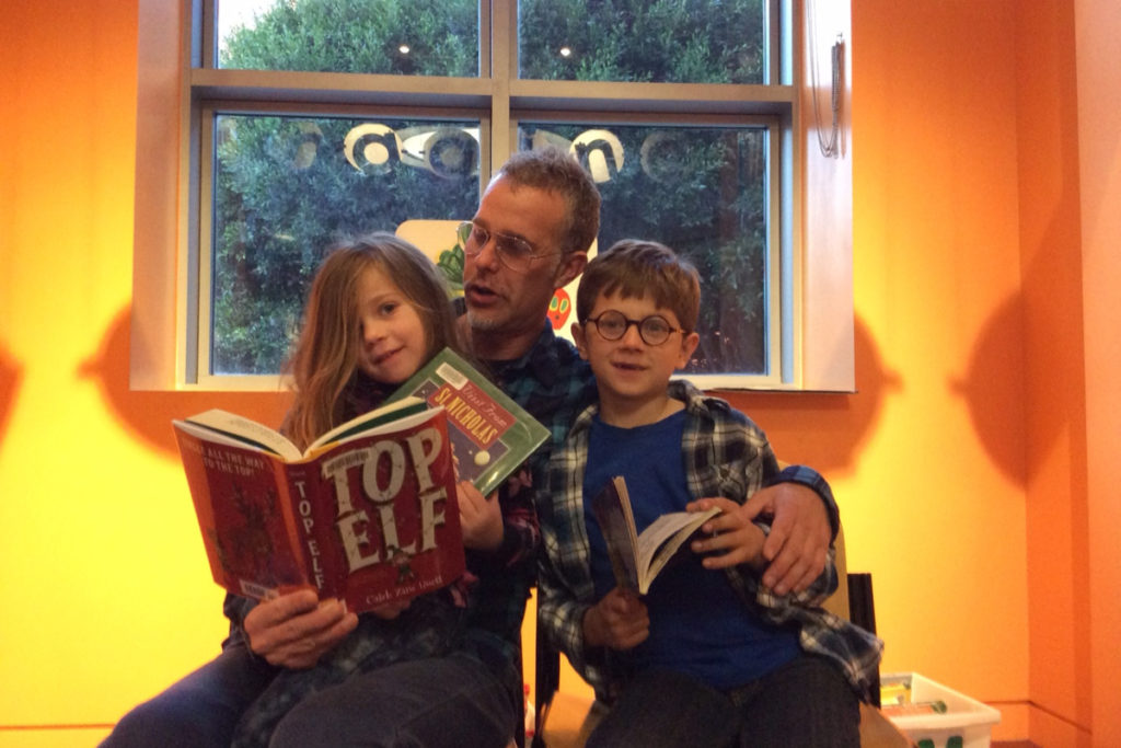 Image description: Andrew Dertien sits with his two children by the window, and appears to be reading aloud from a kids book. Each child holds a book as well.