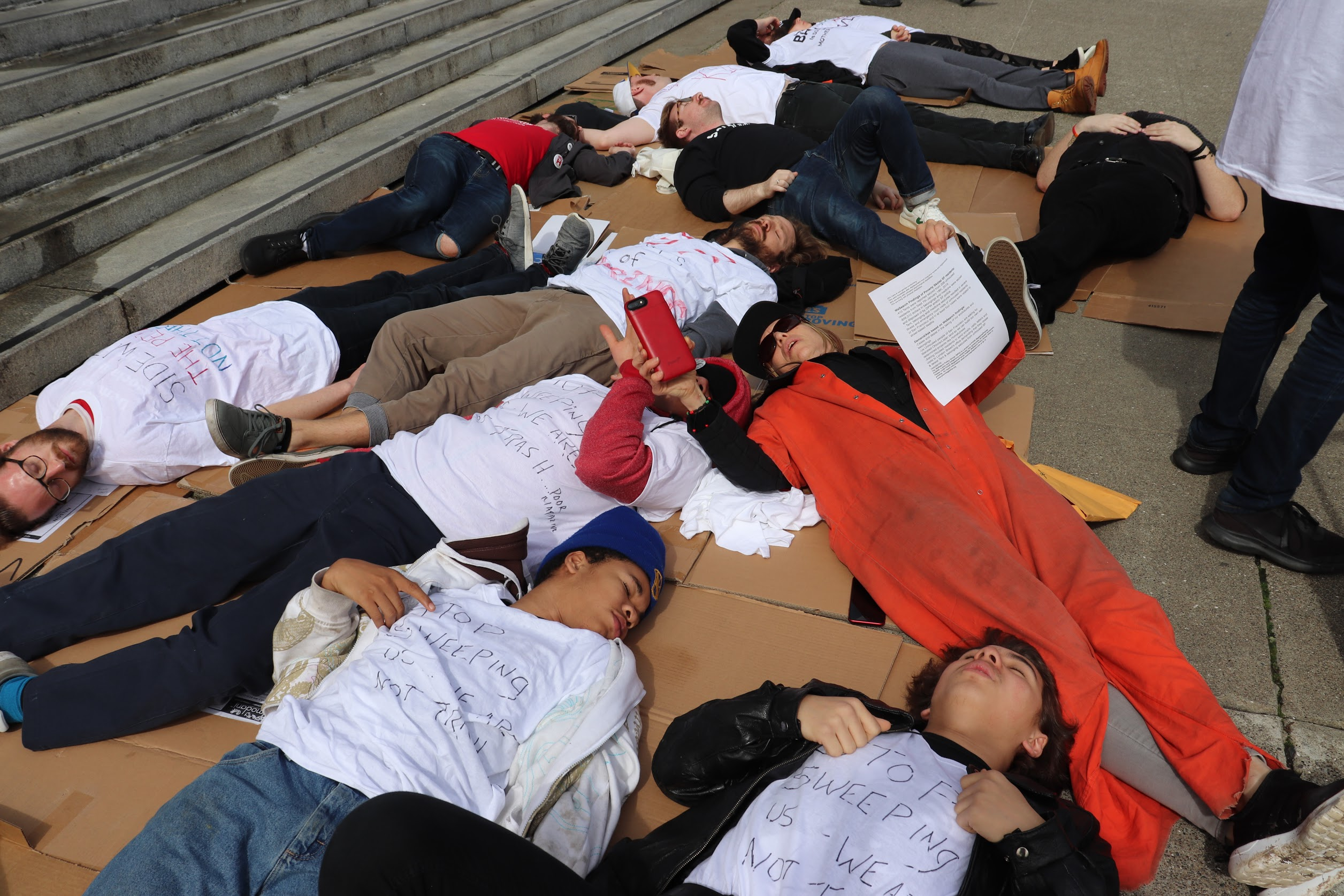 "Activists lie on the ground in protest of the city's inhumane homeless ""sweeps"""