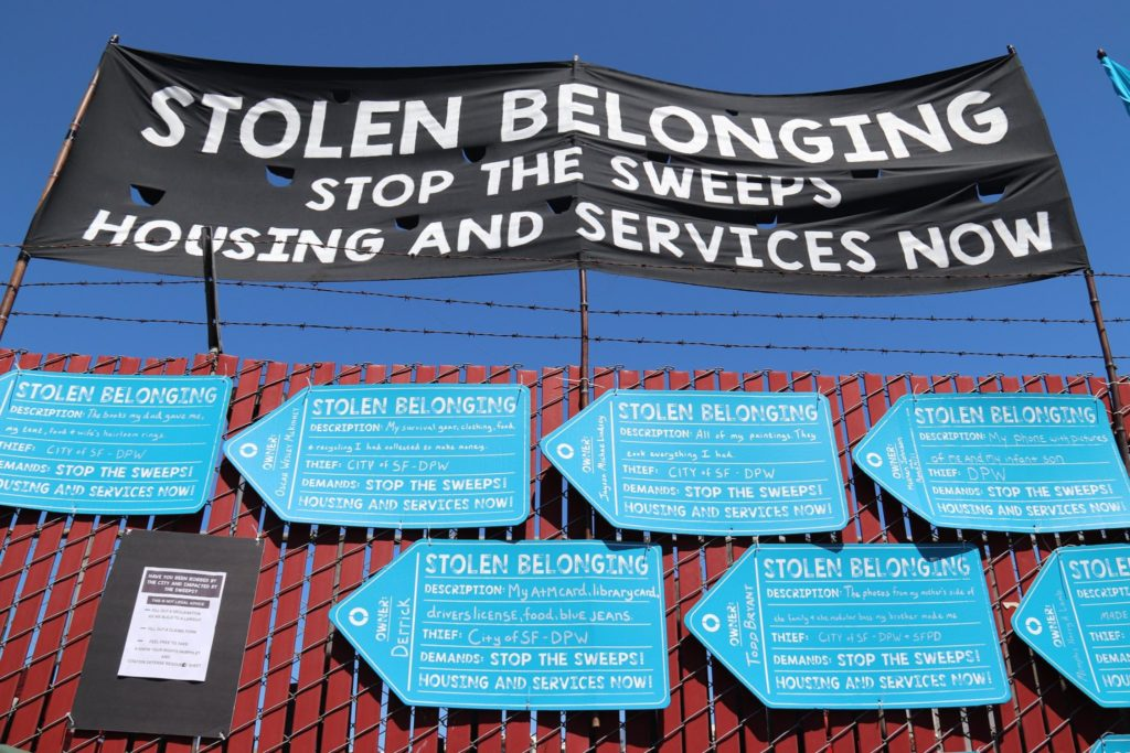 "A banner reading ""Stolen Belonging"" is set up over placards shaped like tags describing the belongings stolen from homeless San Franciscans"