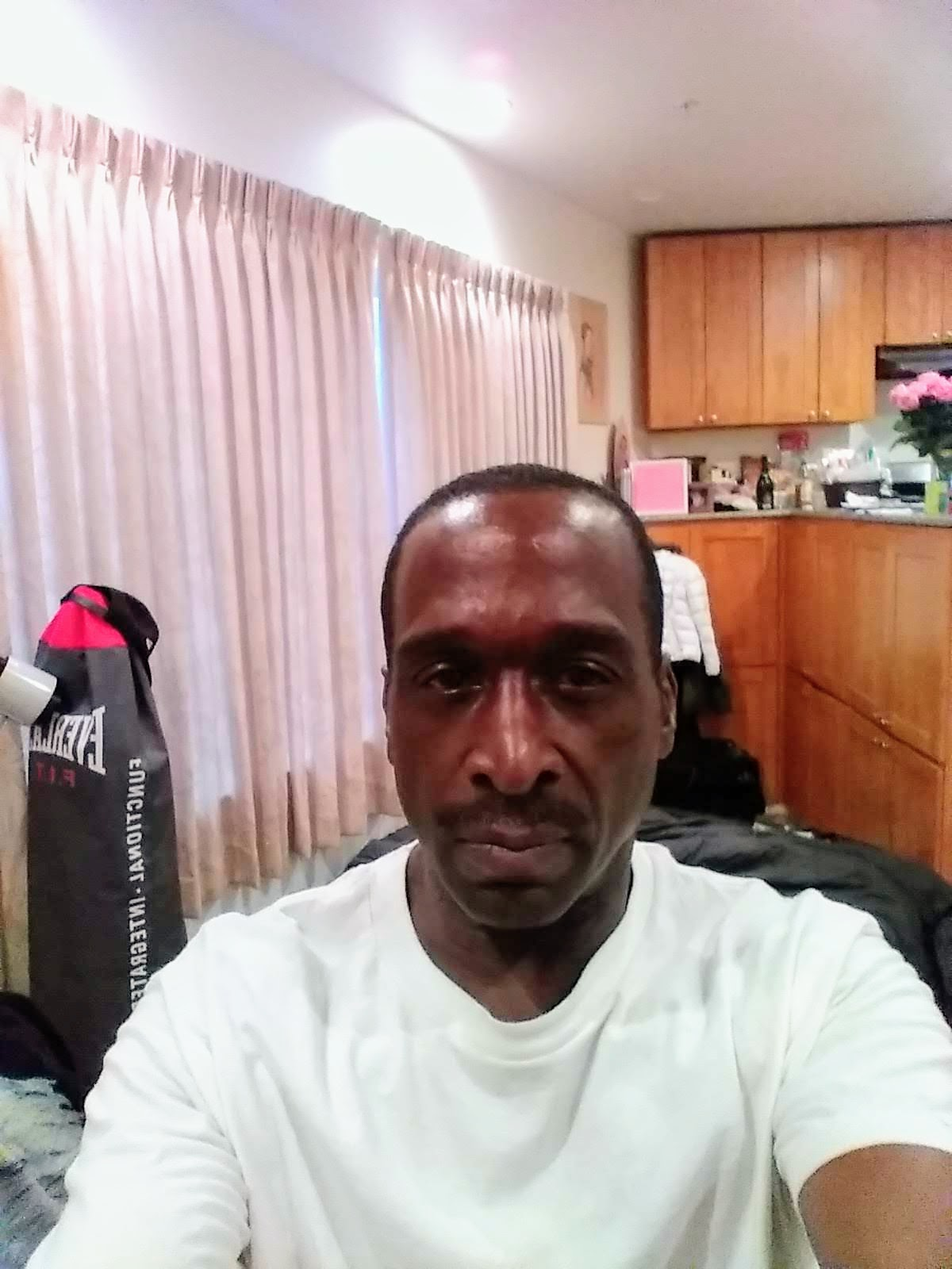 Selfie of a man in a white shirt in a room with bright curtains and wood cabinets in the background.