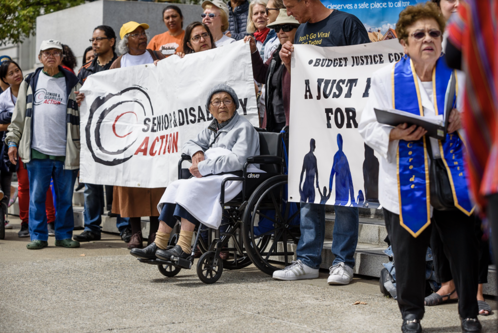 Advocates surround a Senior & Disability Action and a Budget Justice banner