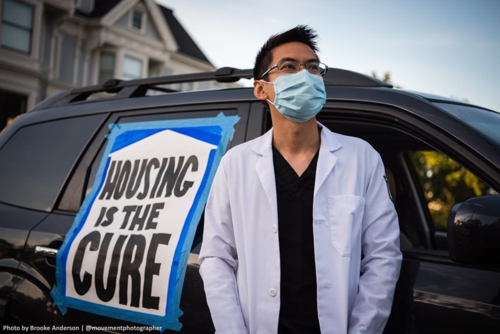 "A person in a doctor's coat and face mask is in the foreground, behind them a vehicle with a sign taped to it that reads ""HOUSING IS THE CURE"""
