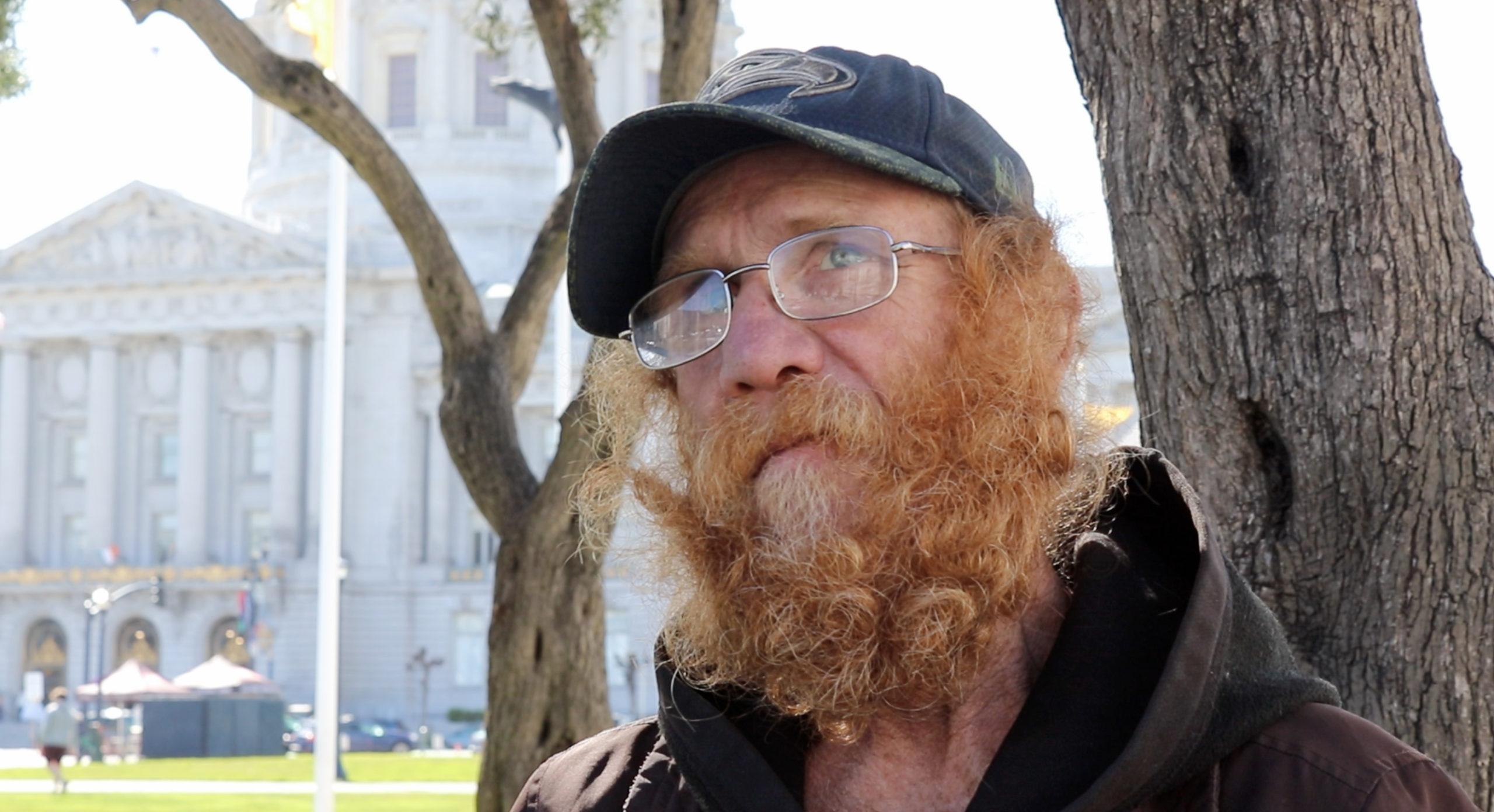Charles Davis with a baseball cap, glasses, and a bushy red beard.