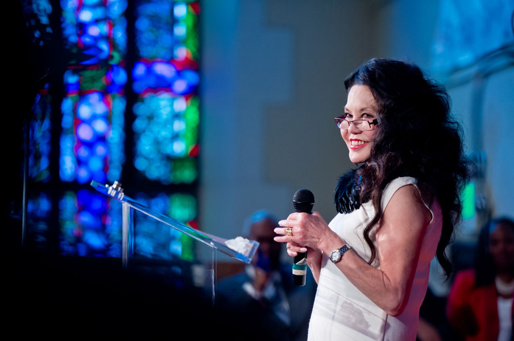 Janice Mirikatani stands holding a microphone and smiling at a glass podium. Behind her is a window of stained glass that suggests she is in a church.