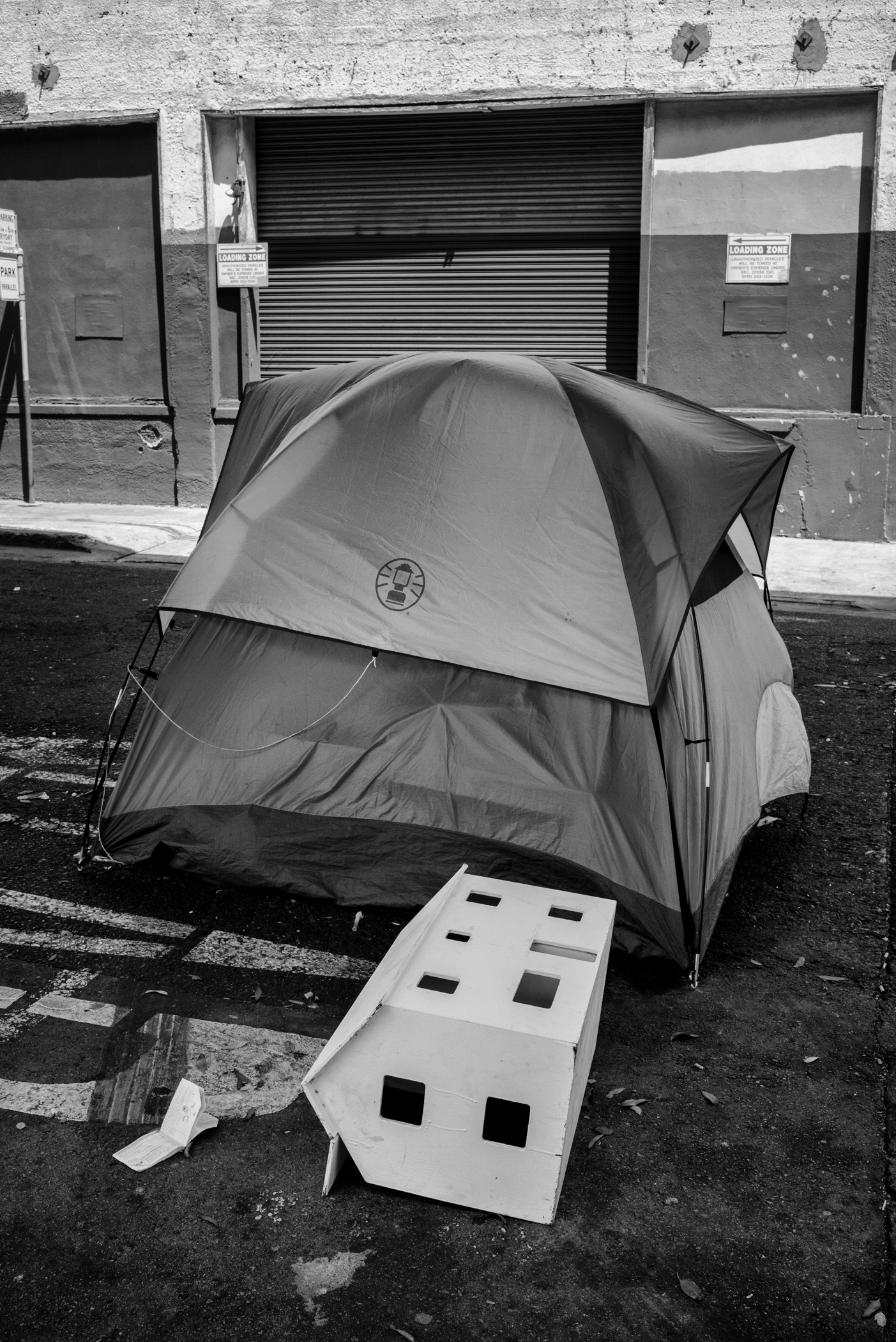 A tent is in the center of the frame. In front of it is what looks like a white dollhouse, laying flat on the ground. The image is in Black and White